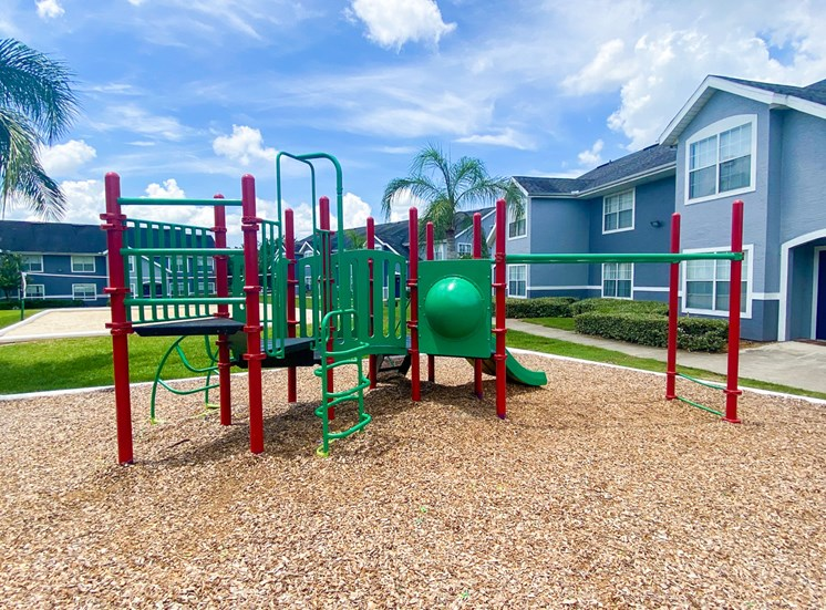 Green and red Playground set in a bed of mulch with buildings and palm tree in the background