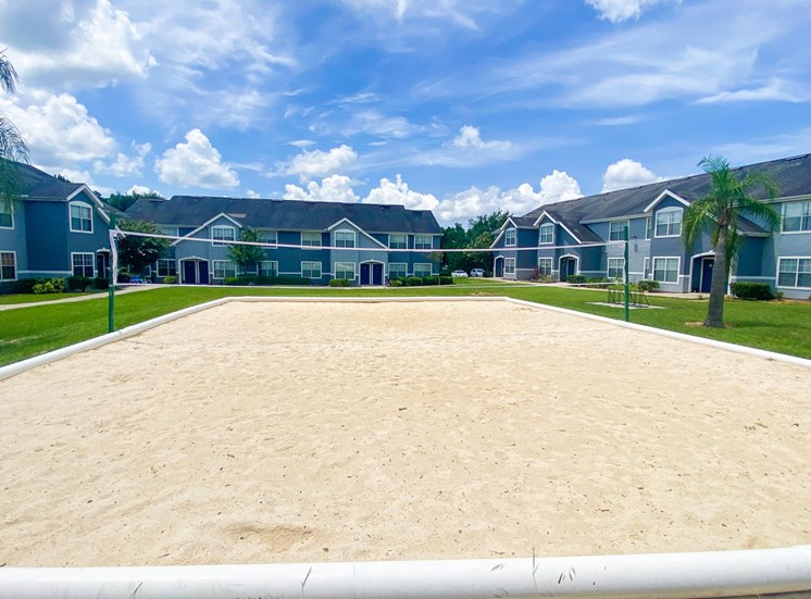 Sand volleyball court with trees and building exteriors  in the background