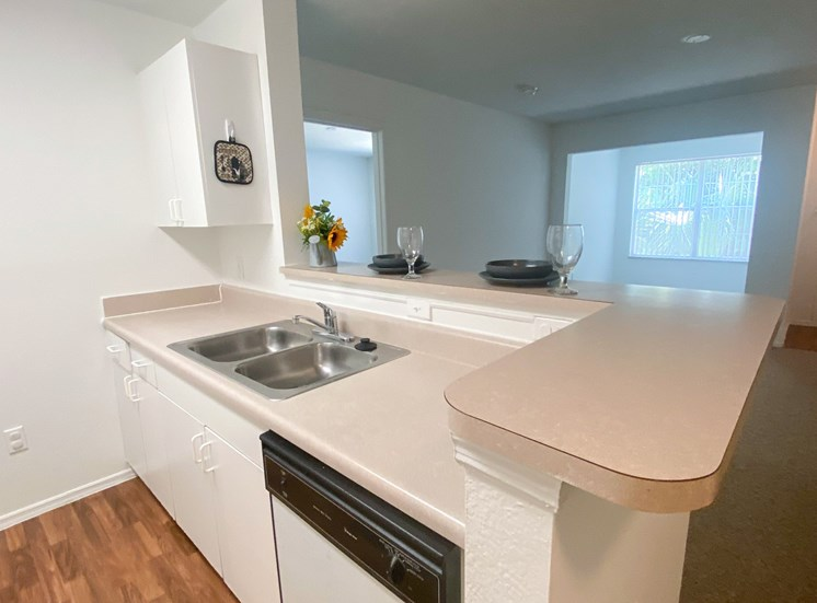 Kitchen featuring white cabinets, white dishwasher, brown vinyl counter top, with place setting plate, bowl and long stem wine glass along with flowers on breakfast bar top, with view of living room