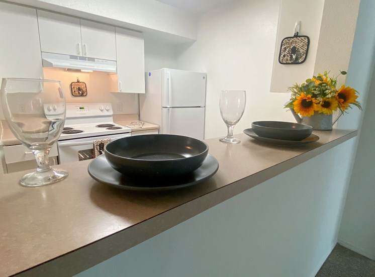 Kitchen featuring white cabinets, white appliances, brown vinyl  counter top, vent hood over electric stove, with place setting plate, bowl and long stem wine glass along with flowers on bar top