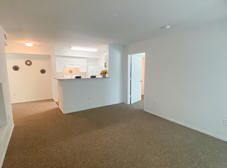Carpeted Living Room with kitchen/dining room view,  fluorescent tube lighting in kitchen