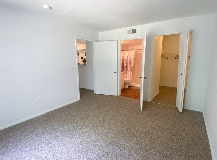 Carpeted Bedroom with view of ensuite bathroom and closet