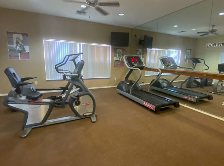 Fitness center with mirrored wall, treadmill, exercise bike, and tv mounted on wall