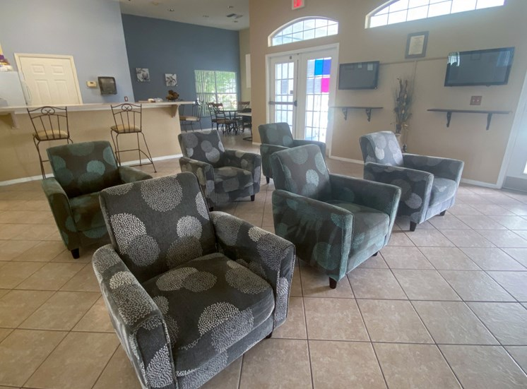 Six arm chairs in clubhouse with two flat screen televisions to the side of them, and the kitchen and dinning room in the back ground on a tile floor, two tone paint