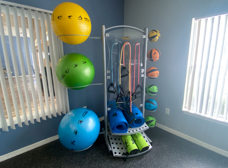 Fitness center equipped with yoga mats, weighted medicine balls, and resistant bands