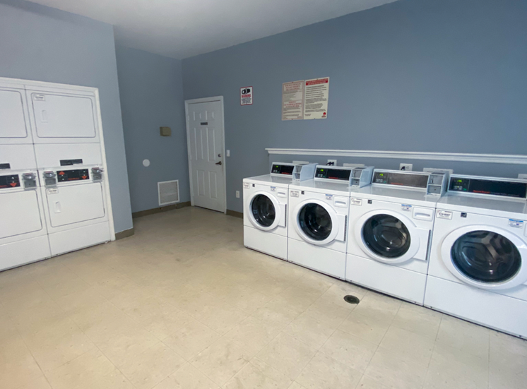 Resident clothing care center with washers, dryers, and tiled flooring