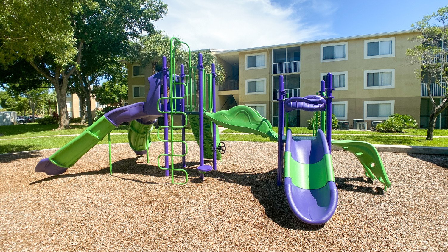 Purple and Green Playground on Mulch with Building Exterior in the Background
