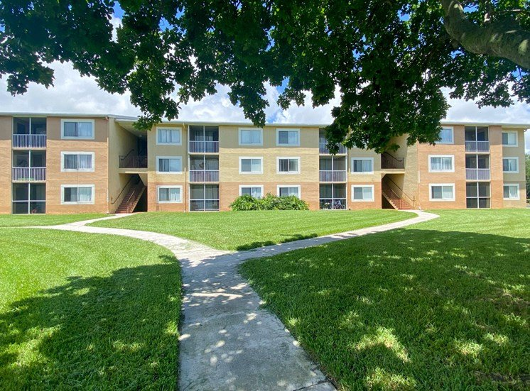 Apartment Building Exterior with Walkway Shaded by Trees