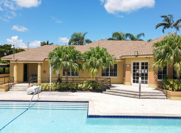Swimming Pool with Sundeck, Lounge Chairs and Palm Trees Next to Leasing Office