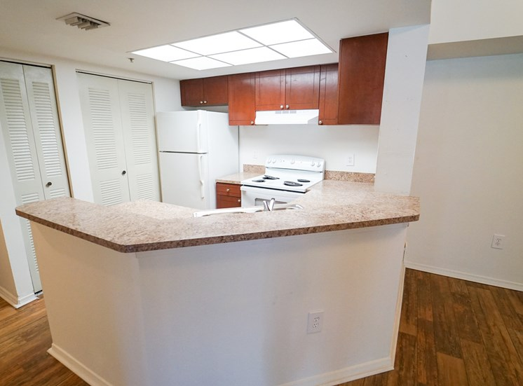 Breakfast Bar off Kitchen with White Appliances, Wood Cabinets and Tan Counters