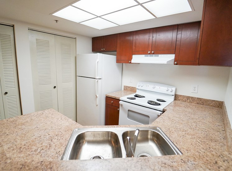 Kitchen with White Appliances, Wood Cabinets and Tan Counters