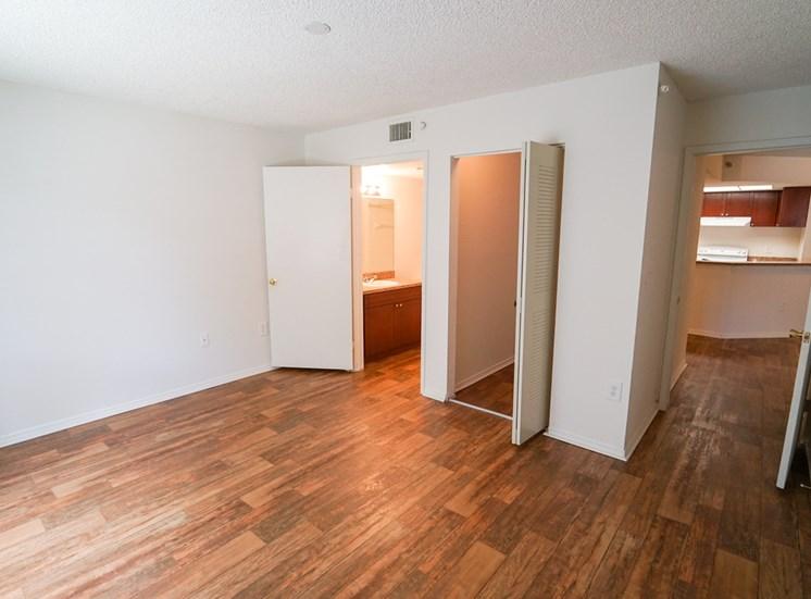 Bedroom with Hardwood Style Flooring and Open Empty Closet Next to En Suite Bathroom