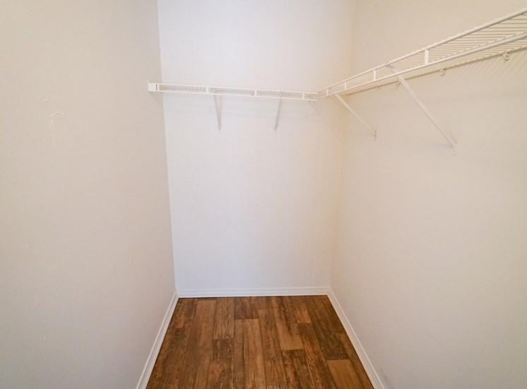 Large Closet with Hardwood Style Flooring and Wired Shelving