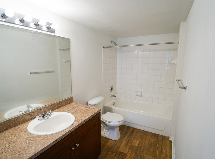 Bathroom with Tan Counters, Wood Cabinets and Toilet Next to White Tiled Shower with Bathtub