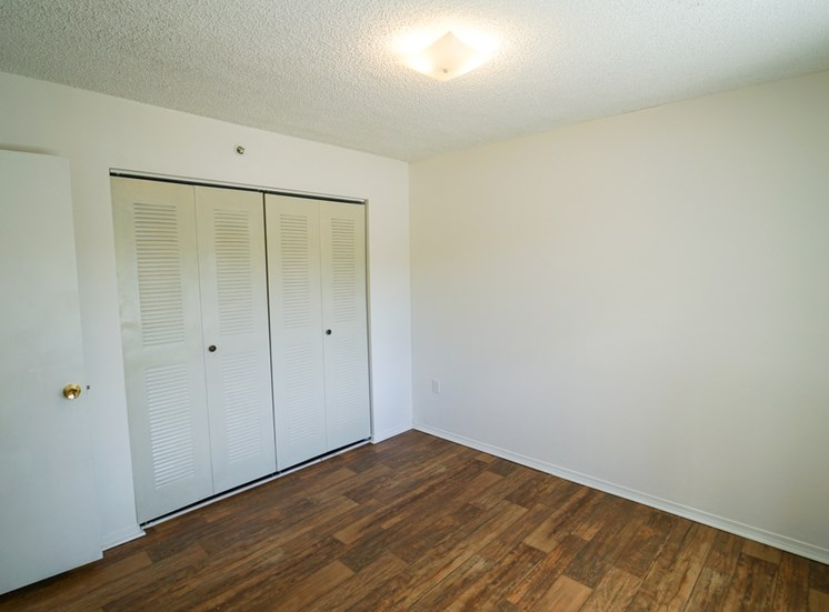 Bedroom with Hardwood Style Flooring and Closet with Sliding Doors