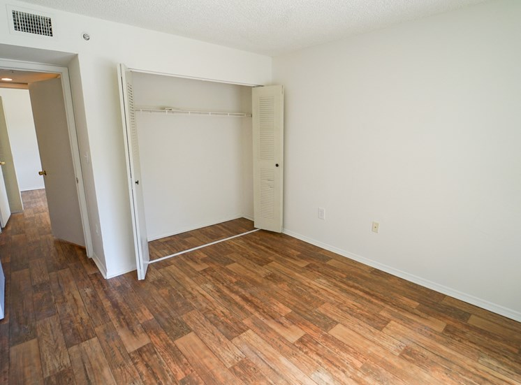 Bedroom with Hardwood Style Flooring and Open Empty Closet with Sliding Closet Doors