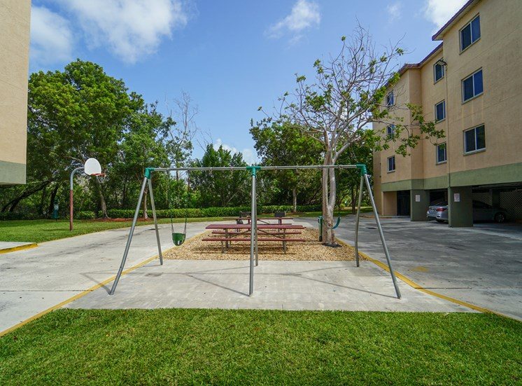 Swing Set in Front Of Picnic Tables Between Building Exteriors