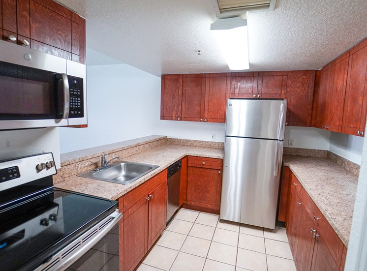 Kitchen with Wood Cabinets, Tan Counters and Stainless Steel Appliances