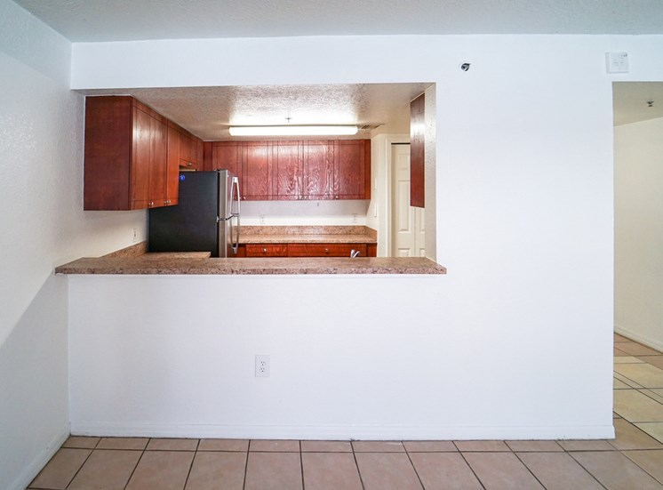 Breakfast Bar Connected to Kitchen  with Wood Cabinets, Tan Counters and Stainless Steel Appliances