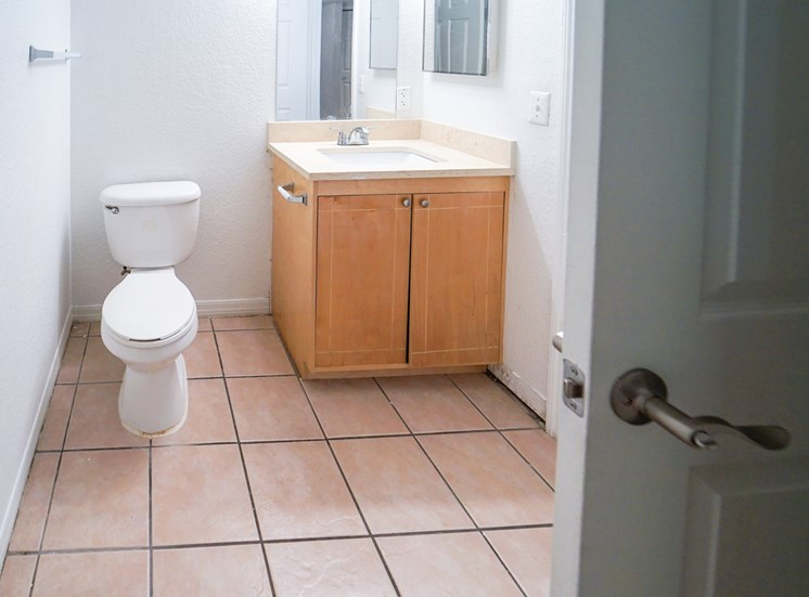 Tiled Bathroom with Light Wood Cabinets and Beige Counter Next to Toilet