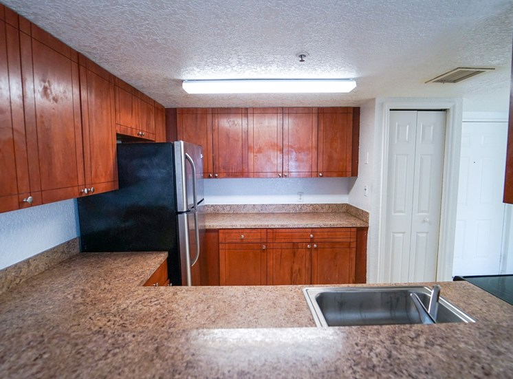 Kitchen with Breakfast Bar, Wood Cabinets, Tan Counters and Stainless Steel Appliances