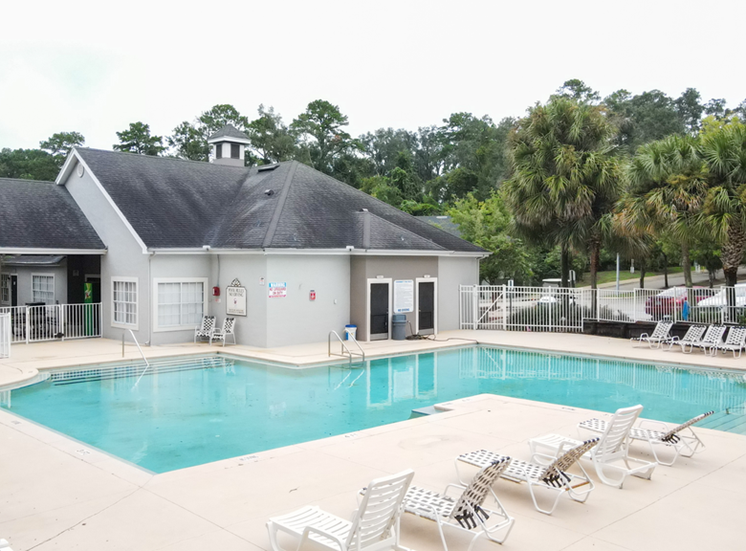 Swimming pool with lounge seating and clubhouse in the background