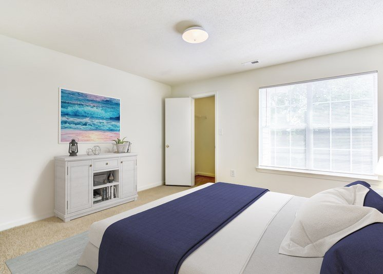 A virtually staged bedroom with white walls, carpet throughout, a large picture window with blinds and a door opening to a closet. It is staged with a gray credenza with art work hanging above, a queen size bed with gray and navy bedding and a gray area rug underneath the bed.