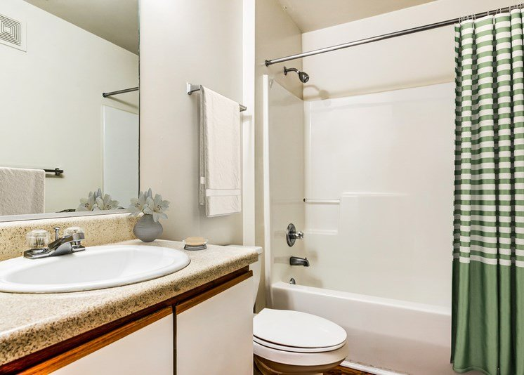 A virtually staged bathroom with white walls, hardwood style flooring, a single toilet, towel bar, a single sink with storage below and a mounted mirror behind the counter/sink area. There is a tub/shower combo with a green and cream checkered shower curtain, a cream towel, and a small vase with flowers on the bathroom countertop.