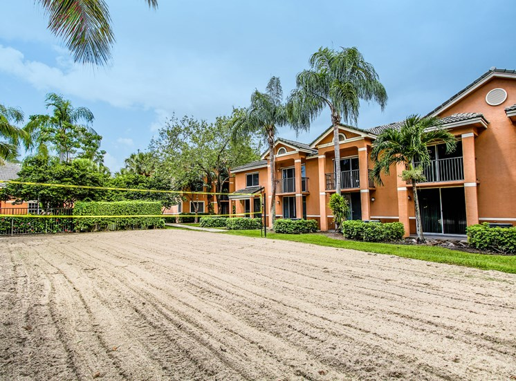 Sand volleyball court surrounded by grass, palm trees and building exteriors