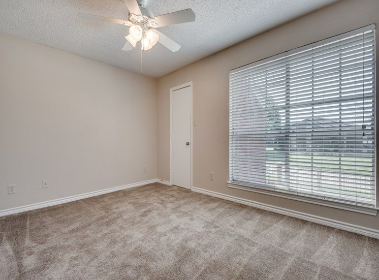carpeted living room with a large window and a ceiling fan