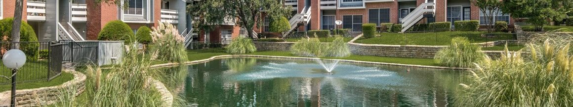 Large pond water fountain in an enclosed area in between the apartment buildings
