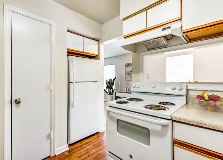 A vacant kitchen with white walls, hardwood style flooring, light countertops, a pantry door, white cabinets with light wood trim, and white appliances including a refrigerator and a stove/oven combo. There is a breakfast bar located behind the stove, and a bowl of fruit sits on the countertop.
