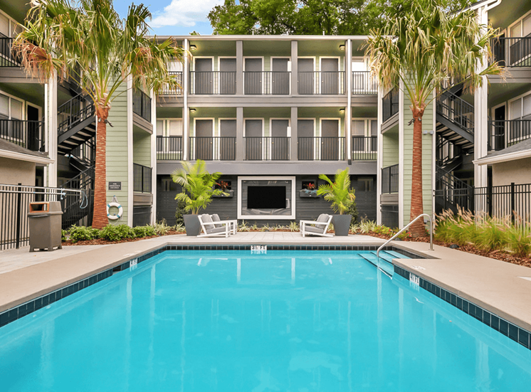 Swimming pool with lounge, wall mounted television, palm trees, and apartment building exterior in the background