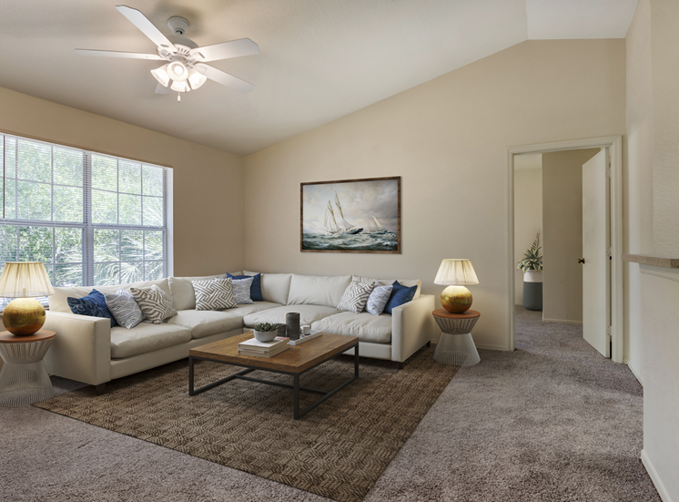 Furnished living room with couch, chair, coffee table, decorative wall art, dining room area in the background