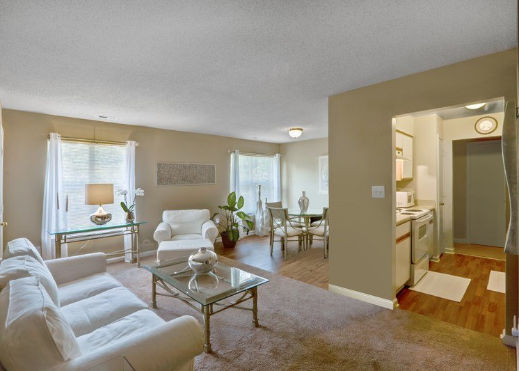 A furnished living and dining room area featuring tan walls with white trim, carpet throughout the living room with hardwood style flooring in the kitchen and dining areas, and two large picture windows with blinds. The living room is furnished with a white sofa, glass top coffee table, a single white chair, a glass top credenza with lamp, and curtains hanging from the window.