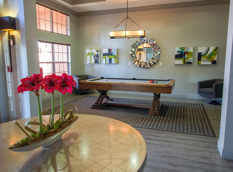 Resident Clubhouse with large table, decoration with flowers, billiards table, two chairs, and wall decor