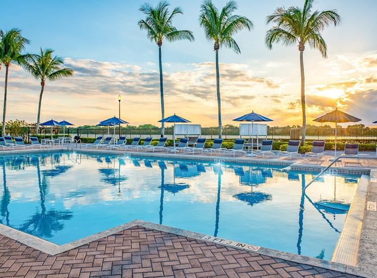 Swimming Pool with Sundeck, Lounge Chairs, Umbrellas and Palm Trees at Sunset