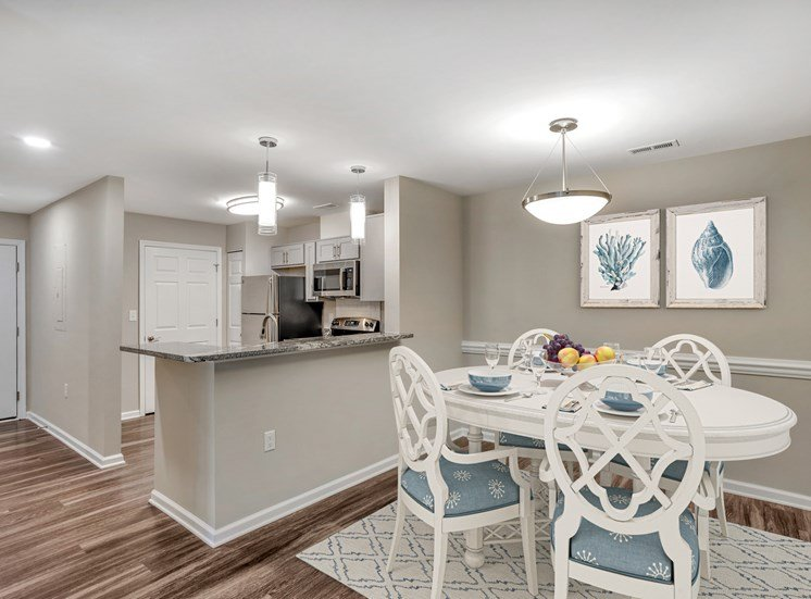 A virtually staged dining room with gray walls with white trim, hardwood style flooring and a pendant light in the center of the ceiling. A kitchen with granite countertops and stainless steel appliances is located in the background.