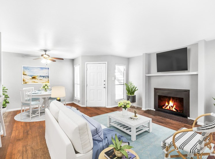 Living room with fireplace dining room with a table in  the background and ceiling  fan