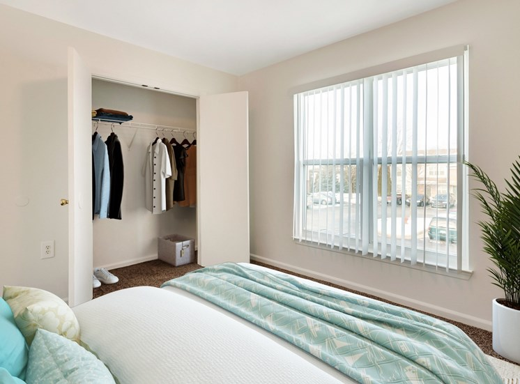 Bedroom with queen size bed. Closet with wire shelves with clothes hangers