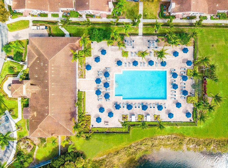 Aerial View of Swimming Pool and Sundeck with Umbrellas and Lounge Chairs Next to Leasing Office