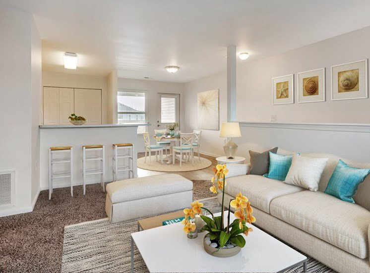 Living room with sofa and coffee table and Breakfast bar with stool by the kitchen with a dinging room table with chairs