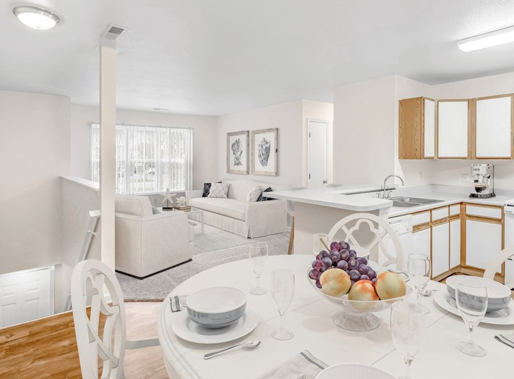 Dining room with large dining table with the kitchen and living room in the background
