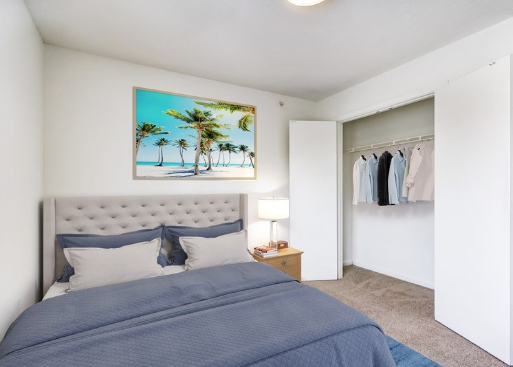 A virtually staged bedroom with white walls and gray carpet throughout, with a standard closet with double doors. It is staged with a queen gray upholstered bed with navy blue and gray bedding, a single wood night stand with lamp, and framed artwork hanging above the bed