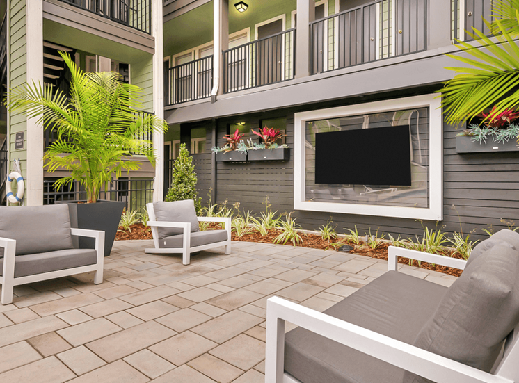 Courtyard lounge with chairs, wall mounted television, surrounded by native landscaping