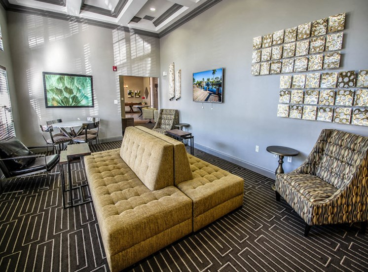 Resident Clubhouse with large couch, three chairs, dining table with four dining chairs, end tables and wall decor