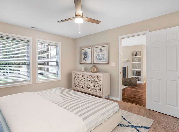 A virtually staged bedroom with the living room located in the background. The bedroom features gray walls with white trim, carpet throughout, two single windows with blinds, a three blade ceiling fan, and a door that opens to the living room.
