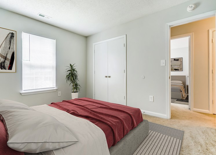A virtually staged bedroom with white walls, carpet throughout, double doors opening to a closet, a single window with blinds, and an entry door leading to the hallway. It is staged with a gray area rug, a queen bed with burgundy and gray bedding, a green plant in the corner of the room and framed artwork hanging on one wall. The 2nd bedroom across the hall is in  the background.