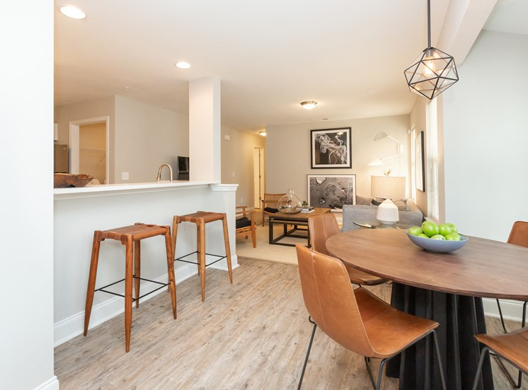 Furnished Model Dining Room with Contemporary Table and Chairs Next to Breakfast Bar with Bar Stools