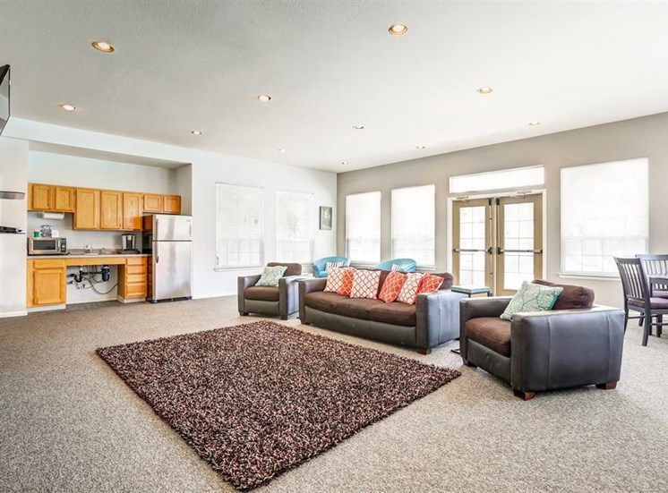 Clubhouse Lounge with Armchairs and Kitchen with Wood Cabinets and Stainless Steel Appliances